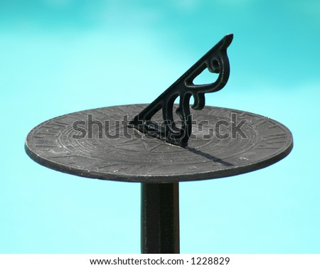 Sundial with pool in background - stock photo