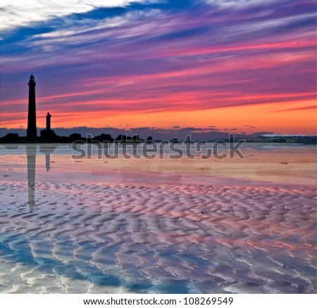 Sundown and lighthouse silhouettes on the beach at Plouguerneau in France - stock photo