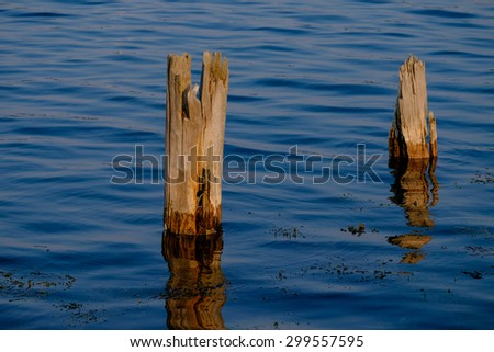 Sundown on the bay with a couple of wooden pilings in the bay - stock photo