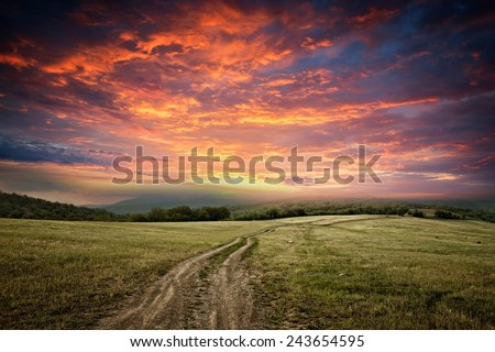 sunet over dirt road - stock photo