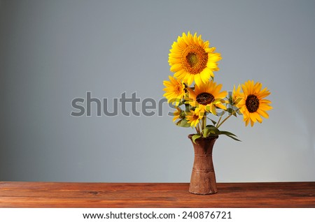 Sunflower in a ceramic vase on a wooden table - stock photo