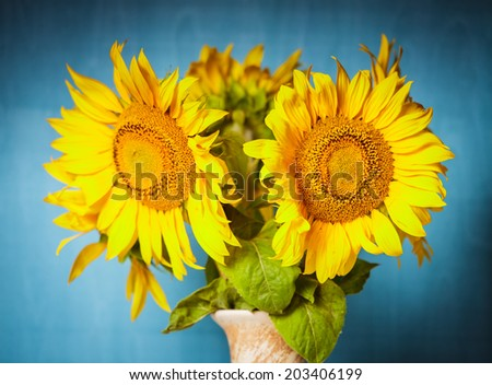 Sunflower in the vase over blue wooden background