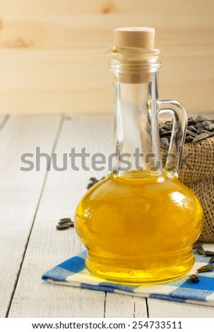 sunflower oil and seeds on wooden background - stock photo