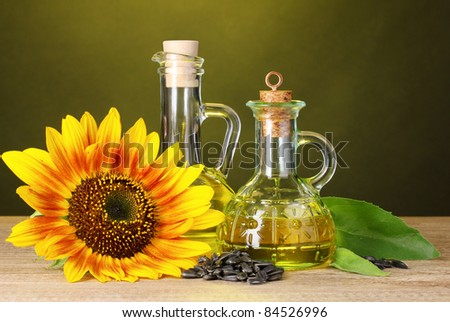 sunflower oil and sunflower on yellow background - stock photo