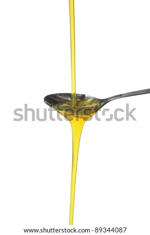 sunflower oil on spoon on white background - stock photo