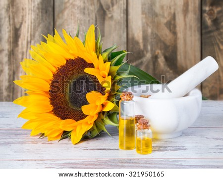 Sunflower oil with flower and seeds on wooden table with nature background - stock photo