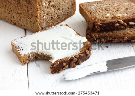 Sunflower seed loaf sliced, cream cheese spread on rustic surface. - stock photo