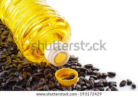 Sunflower seeds and oil in plastic bottle on white background - stock photo