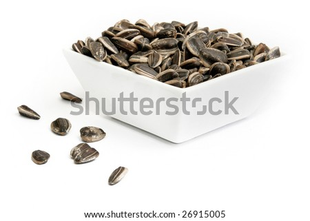 sunflower seeds in a bowl isolated on white background - stock photo