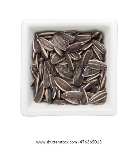 Sunflower seeds in a square bowl isolated on white background
