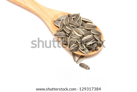 Sunflower seeds with wooden spoon isolated on white background.