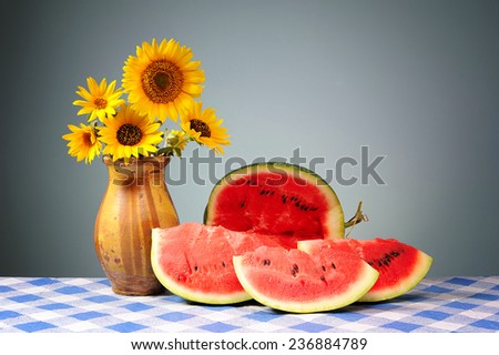 Sunflowers in a vase and sliced watermelon on the table - stock photo