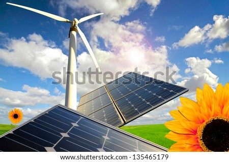 Sunflowers, solar panels and wind turbines in a green field - stock photo