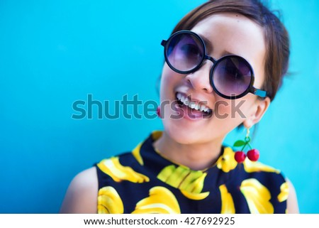 Sunglass Summer girl portrait. Asian woman smiling happy on sunny summer or spring day outside in colourful background. Pretty mixed race Caucasian / Thailand Asian young woman  - stock photo