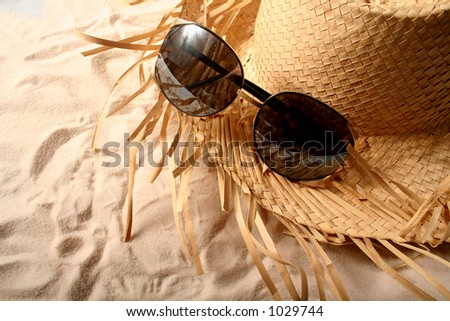 Sunglasses and Straw Hat on Beach - stock photo