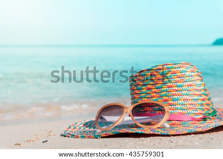sunglasses and straw hat with blur blue sea and sky background -