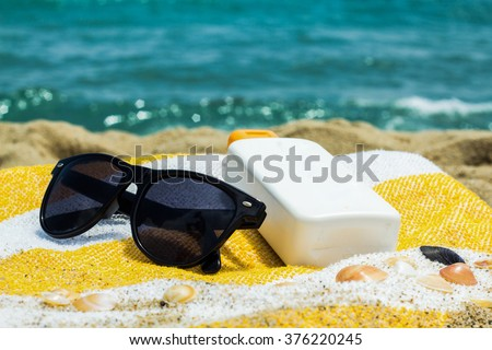 Sunglasses and sunscreen on a striped towel on the background of - stock photo