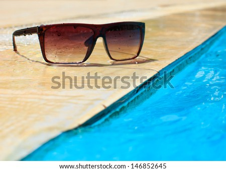 sunglasses by the pool - stock photo