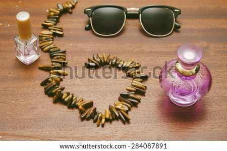 Sunglasses clubmaster, necklase, perfume and nail polish for girl on thw wood old table - stock photo