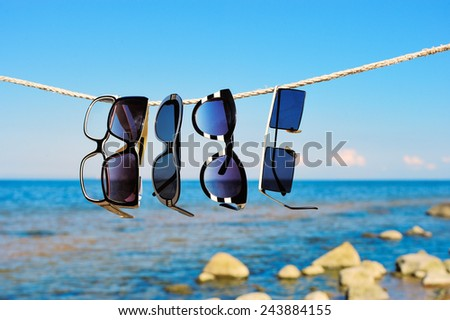 Sunglasses hanging on a rope on a seashore  - stock photo