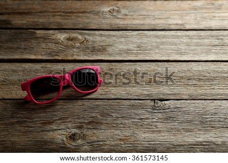 Sunglasses on a grey wooden table - stock photo