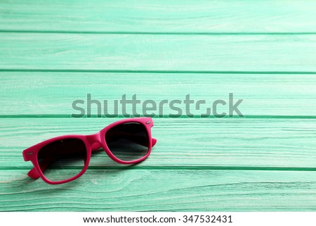 Sunglasses on a mint wooden table - stock photo