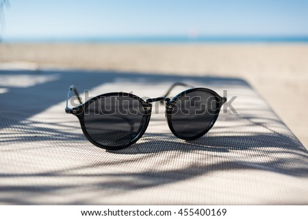 Sunglasses on a sun lounger with sea in front