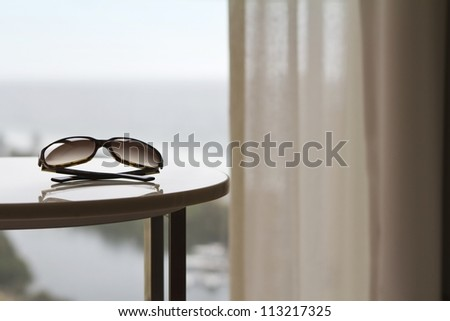 Sunglasses on a table in a luxury hotel room or apartment with blurred view of the ocean behind - stock photo
