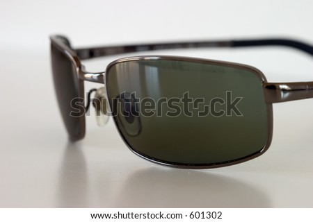 Sunglasses on a white surface, macro view. - stock photo