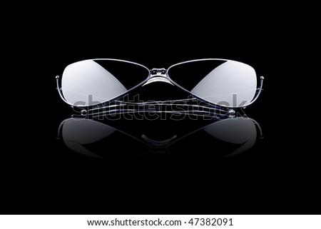 sunglasses on black reflective background - stock photo
