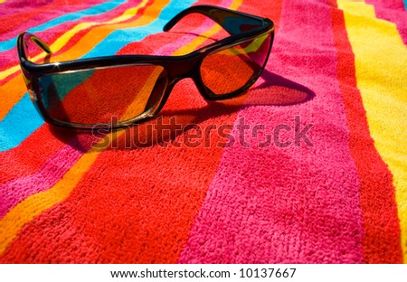 sunglasses on bright beach towel - stock photo