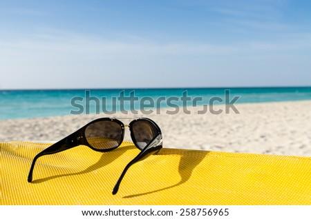 Sunglasses on deckchair, seashore - stock photo