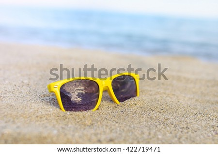 Sunglasses on the beach against the backdrop of the sea. - stock photo