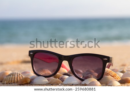 Sunglasses on the beach sea background - stock photo