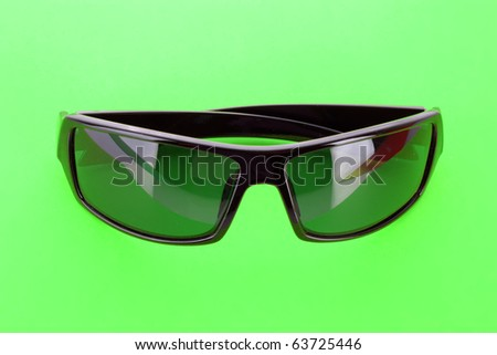 Sunglasses over green - stock photo