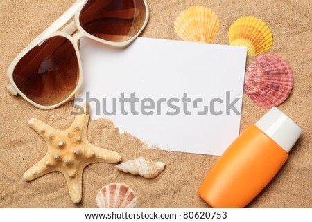 Sunglasses,sunblock and seashells with a blank card on sand. - stock photo