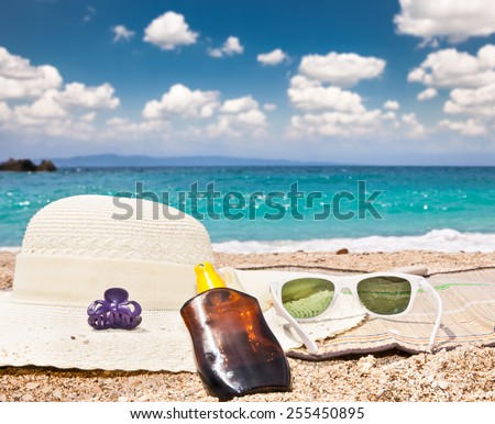 Sunglasses , sunsunhat, suncream on beach. Greece. - stock photo