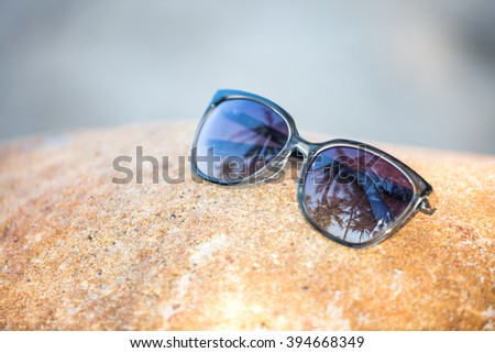 Sunglasses with palm trees reflection. Vacation concept - stock photo