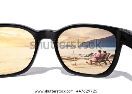 Sunglasses with seascape and couple relaxing on the beach in sunset, vintage tone, isolated on white background