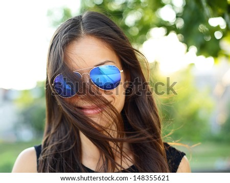 Sunglasses woman funky portrait outdoor with hair flying. Young girl wearing colored sunglasses outside looking at camera smiling happy, Young cool modern multiracial female model girl in her 20s, - stock photo