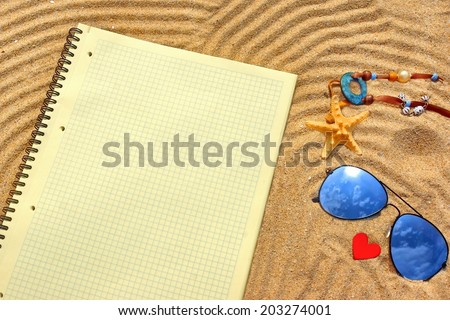 Sunglasses, Yellow checkered notepad and  different objects on the beach sand. Marine Summer Background.