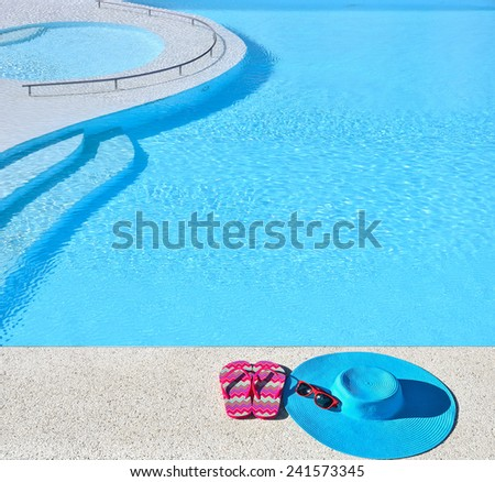 Sunhat with sunglasses and flip-flops beside the swimming pool  --  Concept of vacation  - stock photo