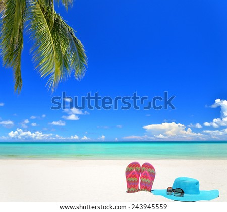 Sunhat with sunglasses and flip flops on the tropical beach -- Beauty on vacation - stock photo