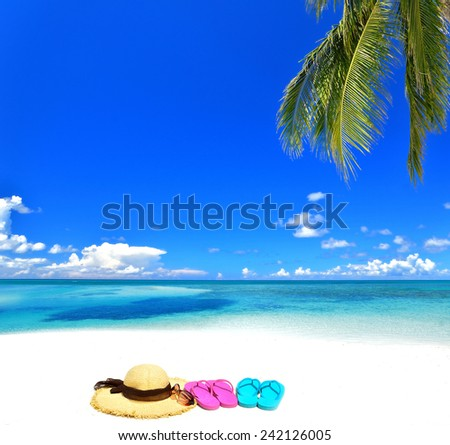 Sunhat with sunglasses and flip-flops on the tropical beach -- Concept of tropical vacation  - stock photo