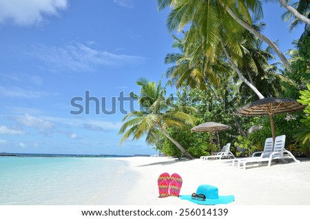 Sunhat with sunglasses and flip flops on white sandy beach -- Tropical beach vacation and travel concept   - stock photo