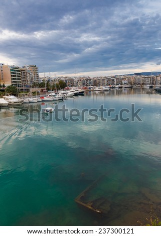 Sunken fishing boat below water, abandoned in the small port of Zea Marina in Greece with passing fishing boat returning in harbor - stock photo