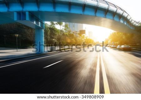 sunlight and empty road through bridge - stock photo