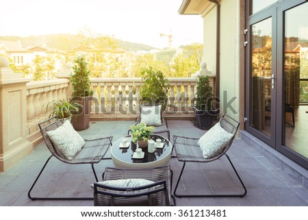 sunlight and table and chairs in modern balcony - stock photo