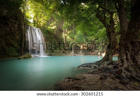 Sunlight beams and rays shine through leaves of trees in tropical rainforest park in Thailand with beautiful waterfall falling in clear pond and old big tree on foreground