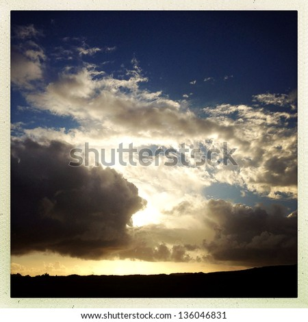 Sunlight behind storm clouds in sky